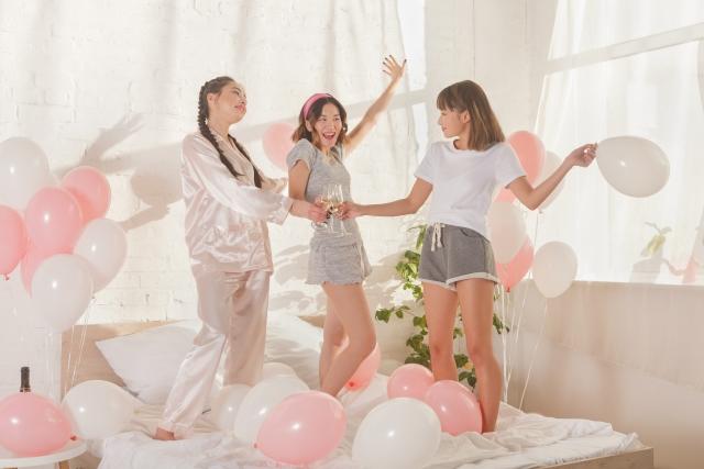 ベッドのうえではしゃぐ女性たち